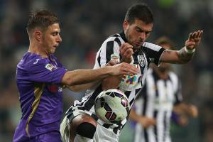 """Fiorentina's midfielder Joaquin Sanchez Rodriguez (L) of Spain fights for the ball with Juventus' midfielder Stefano Sturaro (R ) during the Italian Serie A  football match Juventus Vs Fiorentina on April 29, 2015 at the """"Juventus Stadium"""" in Turin.  AFP PHOTO / MARCO BERTORELLO        (Photo credit should read MARCO BERTORELLO/AFP/Getty Images)"""